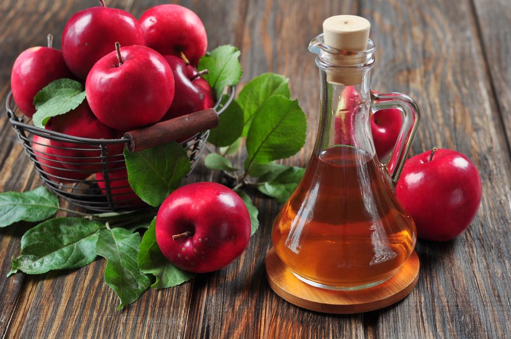 A bowl of apples beside a flask of apple cider vinegar